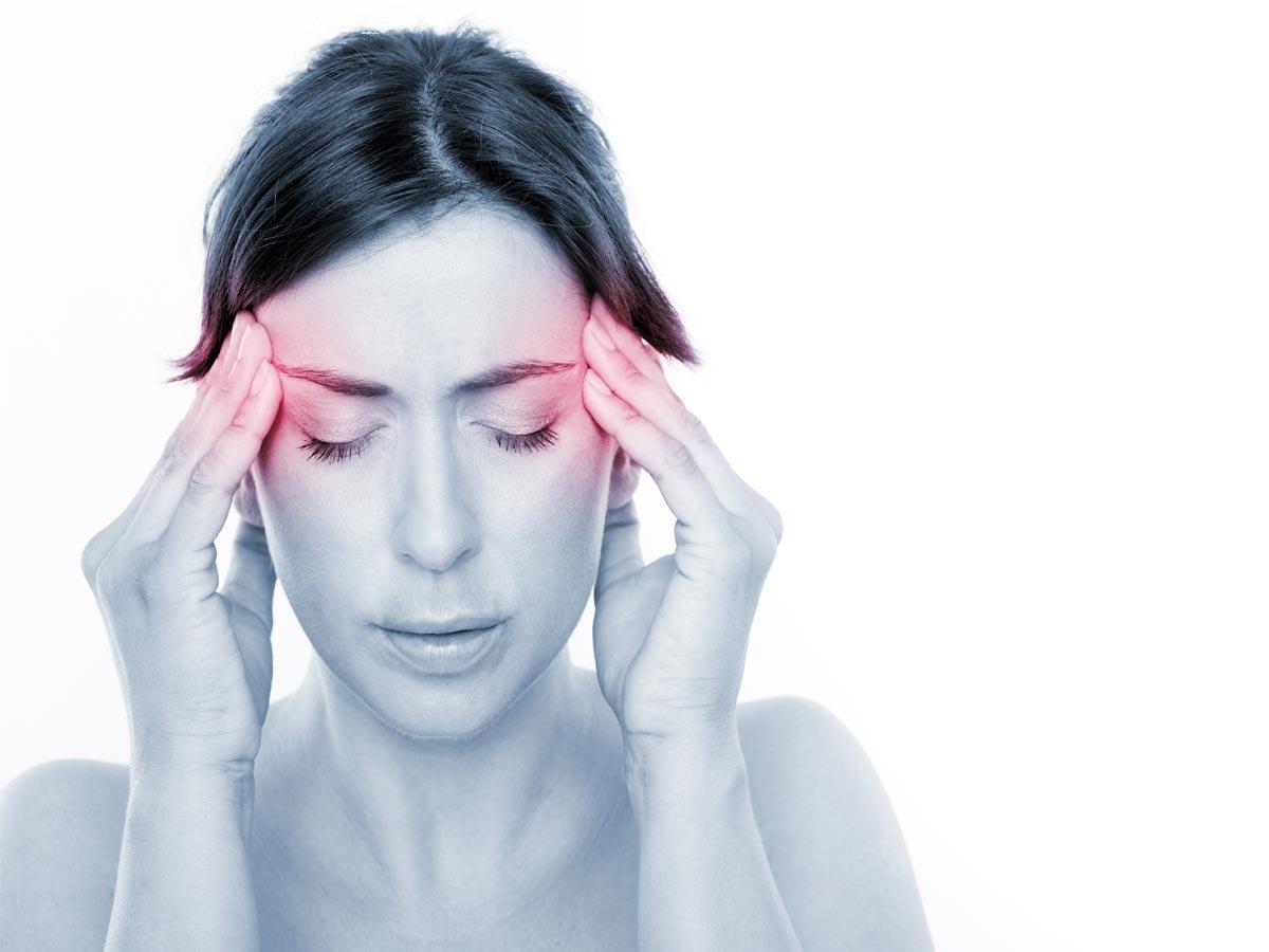 Une femme souffrant de maux de tête et vertiges.