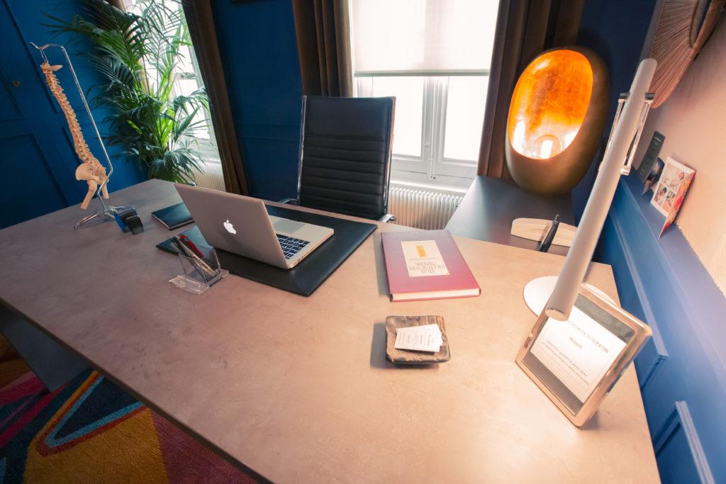 Bureau d'un ostéopathe avec des livres et un ordinateur.